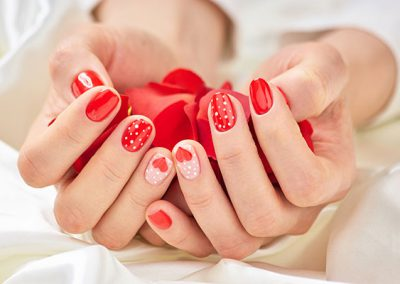 Female manicured hands with rose petals.