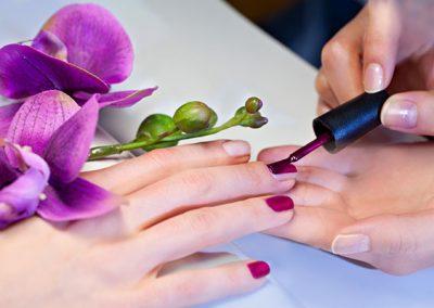 Woman applying nail varnish to finger nails