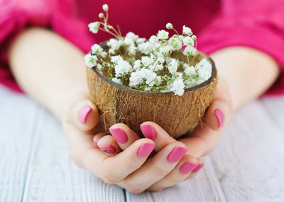Woman cupped hands with pink manicure holding coconut shell full